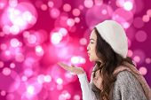 Brunette in winter clothes blowing kiss against light glowing dots on pink