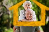 Man giving wife a piggyback against house outline in clouds