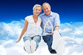 Happy mature couple holding a house shape against bright blue sky over clouds