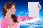 Surprised woman looking at paper against mountain peak through clouds