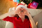 Smiling redhead doing heart sign at christmas at home in the living room
