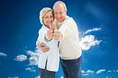 Happy mature couple showing thumbs up against cloudy sky with sunshine