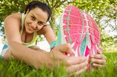 Smiling athletic brunette stretching on the grass in the park