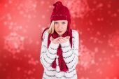 Festive blonde blowing over hands against digitally generated delicate snowflake design