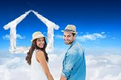 Happy hipster couple holding hands and smiling at camera against bright blue sky over clouds