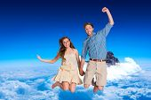 Cheerful young couple jumping against mountain peak through the clouds