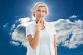 Mature woman thinking with hand on chin against blue sky with clouds and sun