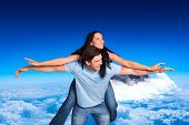 Young man giving girlfriend a piggyback ride against mountain peak through the clouds