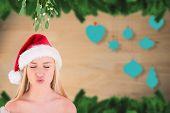 Festive cute blonde under mistletoe against blurred christmas decorations hanging over wood