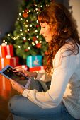 Redhead woman sitting on floor using tablet at christmas at home in the living room