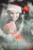 Festive brunette pressing gift at christmas against snowy landscape with fir trees