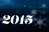 2015 against snowflakes hanging against starry sky