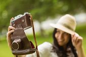 Smiling brunette taking a selfie with retro camera in the park