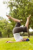 Concentrated brown hair doing yoga on grass