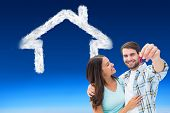 Happy young couple showing new house key against blue sky