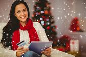 Pretty brunette shopping online on sofa at christmas against twinkling stars