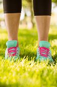 Woman in running shoes standing on grass in the park