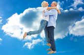 Mature couple hugging and having fun against cloudy sky
