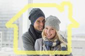 Cute couple in warm clothing smiling at camera against house outline