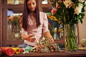 Floral designer tying up flowers with ribbon in shop