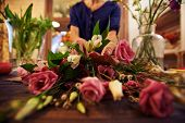 Female florist sorting fresh flowers in workshop