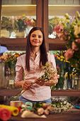 Happy female florist looking at camera in workshop