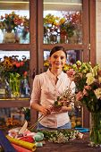 Pretty florist working in shop of fresh flowers