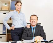 Business woman and happy man together at a desk in their office
