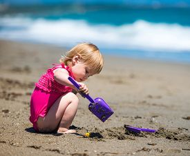 stock photo of shoulder-blade  - little cute girl playing in the sand with a shovel on the beach on a beautiful summer day - JPG