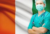 stock photo of ivory  - Surgeon with national flag on background  - JPG