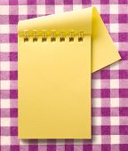 stock photo of blank check  - Open blank yellow notepad with spiral closeup - JPG