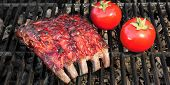stock photo of baby back ribs  - Grilled BBQ Tasty Spicy Smoked Marinated Pork Ribs and Tomatoes - JPG