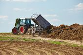 pic of tractor trailer  - Old tractor dumping manure from a trailer - JPG