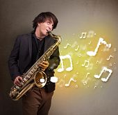 stock photo of saxophone player  - Handsome young musician playing on saxophone with musical notes - JPG