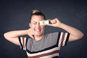 image of gril  - Young girl holding paper with green dollar sign concept - JPG