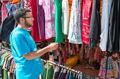 image of thrift store  - Young man buying in second hand store - JPG