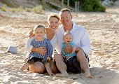 picture of couple sitting beach  - young happy family couple and children sitting on beach sand smiling with blond small baby boy and sweet lovely little girl in summer tourism and holidays concept - JPG