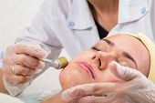 stock photo of face mask  - Beautician working on a face model in a spa salon - JPG