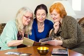 stock photo of close-up middle-aged woman  - Close up Three Middle Age Female Friends Sitting at the Living Area Looking at Photo Album Together and Talking Happy Moment in the Past.