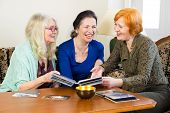 stock photo of memento  - Three Adult Women Friends Relaxing at the Living Area Laughing Together While Looking at their Old Photos in an Album.