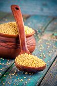 picture of millet  - organic millet seeds in a spoon and a ceramic bowl on wooden table - JPG