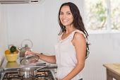 pic of saucepan  - Beautiful brunette looking at saucepan in the kitchen - JPG