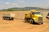 picture of dump-truck  - Tandum dump truck arrives at a new commercial construction development project for its load of dirt - JPG