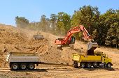 picture of track-hoe  - Large track hoe excavator filling a dump truck with rock and soil for fill at a new commercial development road construction project - JPG