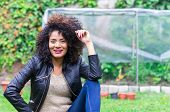 foto of afro hair  - exotic beautiful young girl with dark curly hair relaxing in the garden - JPG