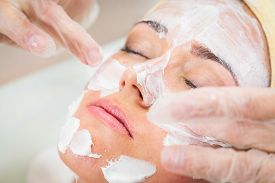stock photo of beauty parlour  - Beautiful woman with facial mask at beauty salon - JPG
