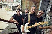 Постер, плакат: Music band outdoor portrait Musicians and woman soloist posing outside against grunge yard black a