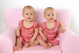 picture of identical twin girls  - Identical ten month old twin baby girls seated on a pink child size sofa - JPG