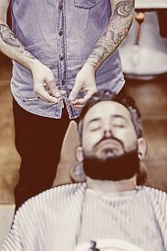 stock photo of barber razor  - view from above of the hands of a barber is choosing razor and a customer sitting on a barber chair on a beard shaving session  - JPG