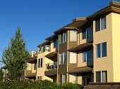 stock photo of brighten  - Late afternoon light brightens the sunny colors of a row of condos - JPG